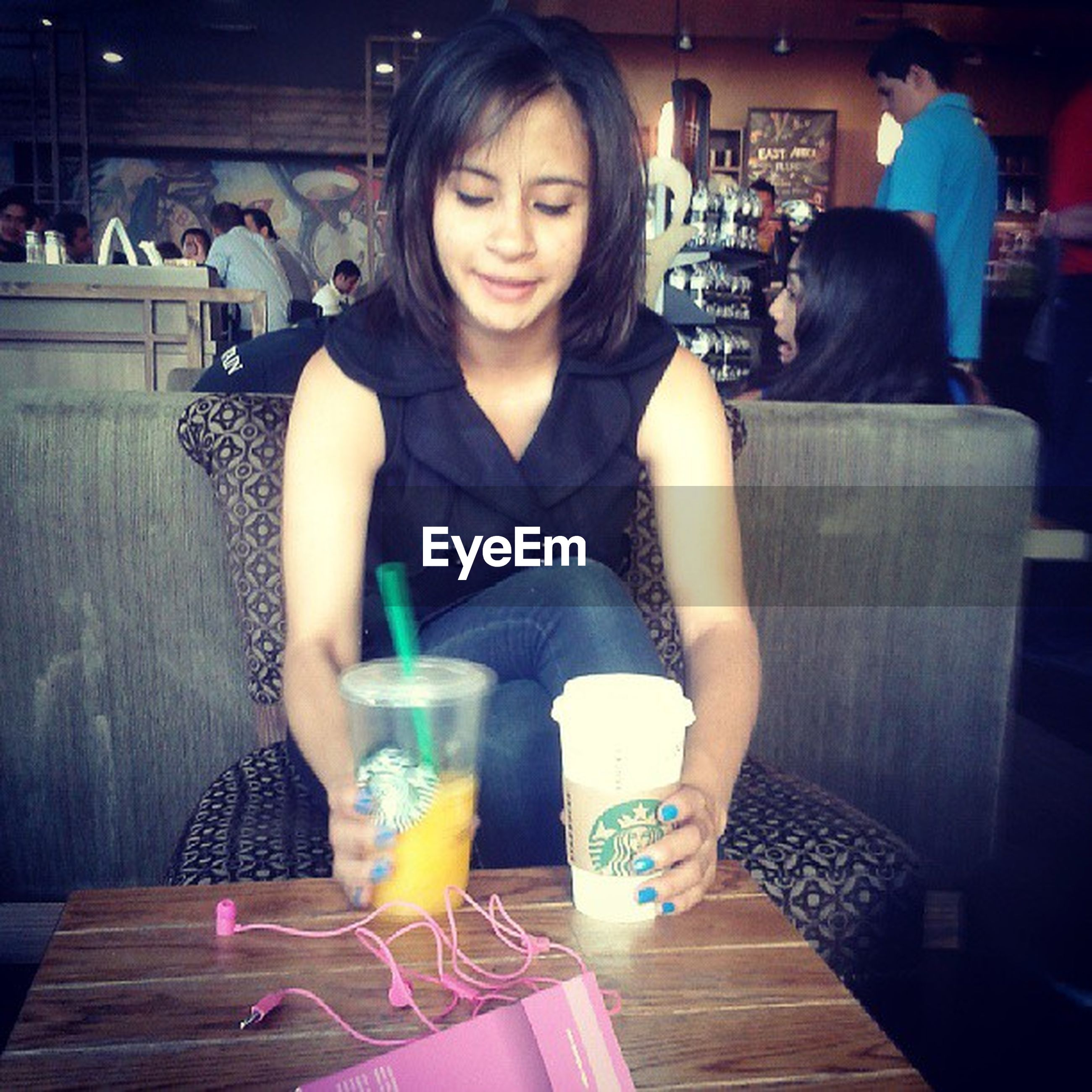 indoors, lifestyles, young adult, casual clothing, person, sitting, leisure activity, table, front view, young women, looking at camera, portrait, food and drink, restaurant, smiling, drink, standing, three quarter length