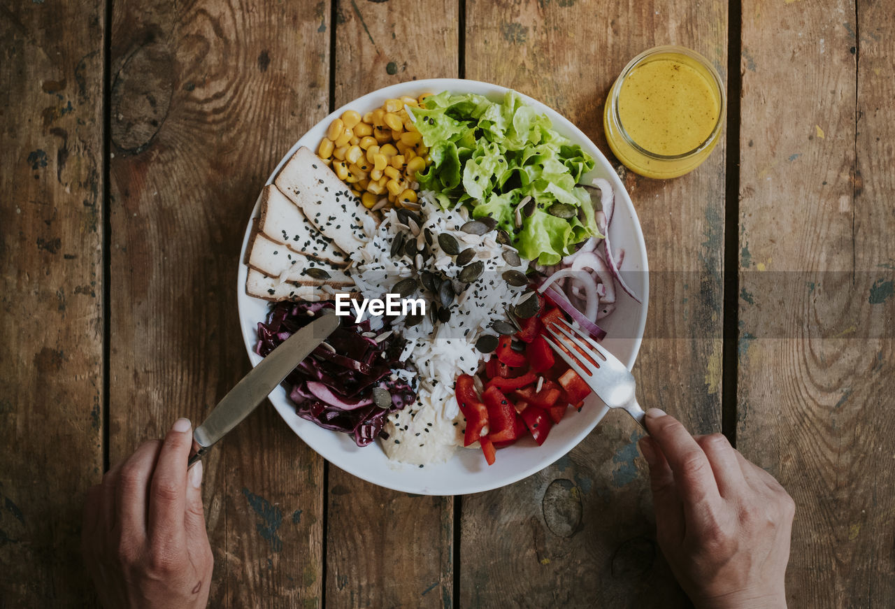 food and drink, healthy eating, food, kitchen utensil, freshness, eating utensil, human hand, hand, wellbeing, directly above, table, bowl, high angle view, indoors, salad, holding, vegetable, one person, wood - material, human body part, meal, finger, vegetarian food