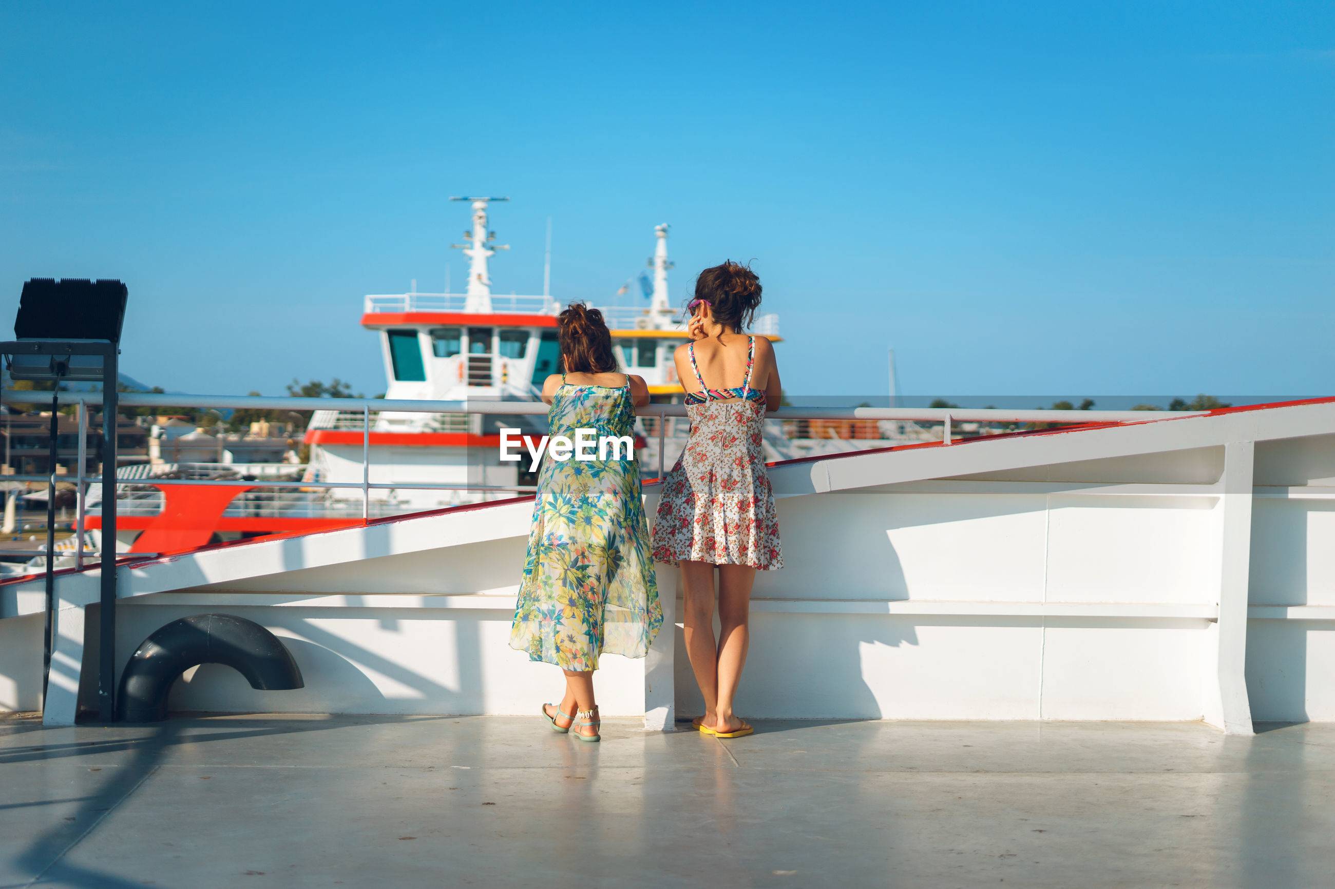 Rear view of women standing by railing on boat against blue sky