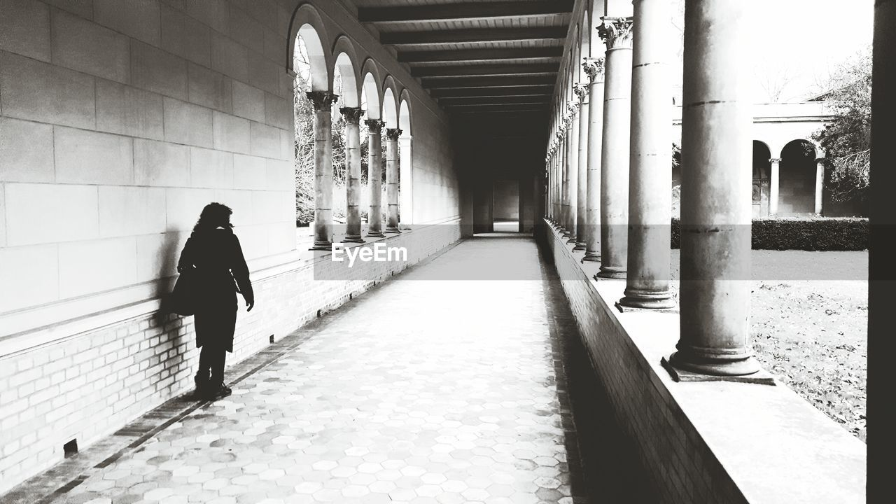 architecture, built structure, walking, direction, one person, the way forward, architectural column, rear view, full length, real people, lifestyles, arcade, men, diminishing perspective, building, day, corridor, leisure activity, footpath, outdoors, colonnade, ceiling