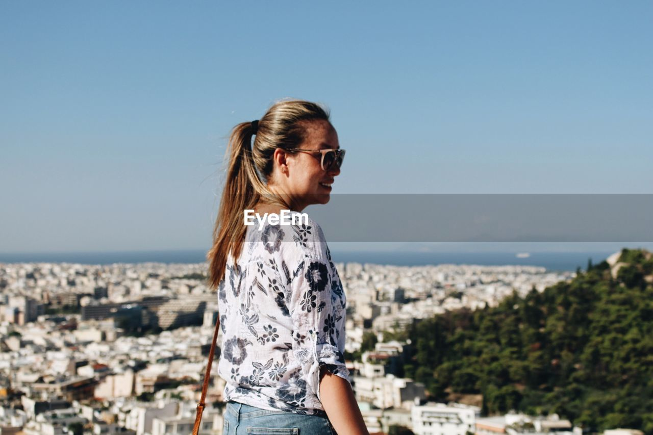 Mid Adult Woman Overlooking Cityscape Against Clear Sky