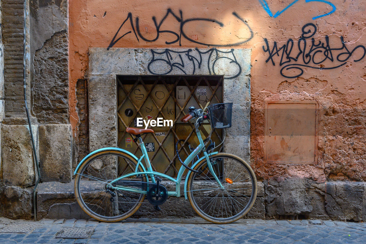 architecture, bicycle, built structure, building exterior, wall - building feature, graffiti, transportation, day, wall, land vehicle, stationary, mode of transportation, no people, outdoors, building, creativity, art and craft, city, window, entrance, stone wall