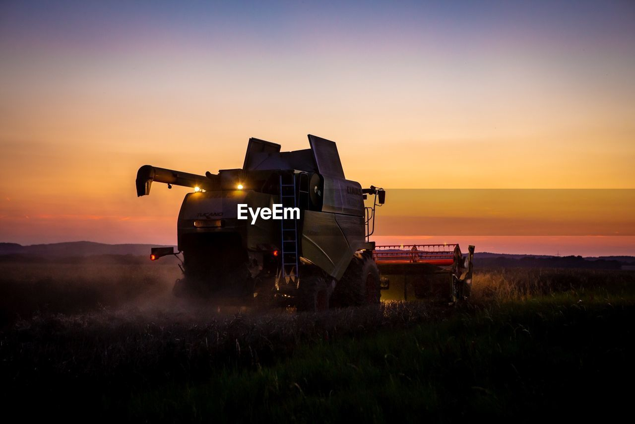 sunset, field, sky, land, nature, orange color, agricultural machinery, landscape, combine harvester, land vehicle, environment, machinery, rural scene, transportation, agriculture, scenics - nature, beauty in nature, mode of transportation, outdoors, farm