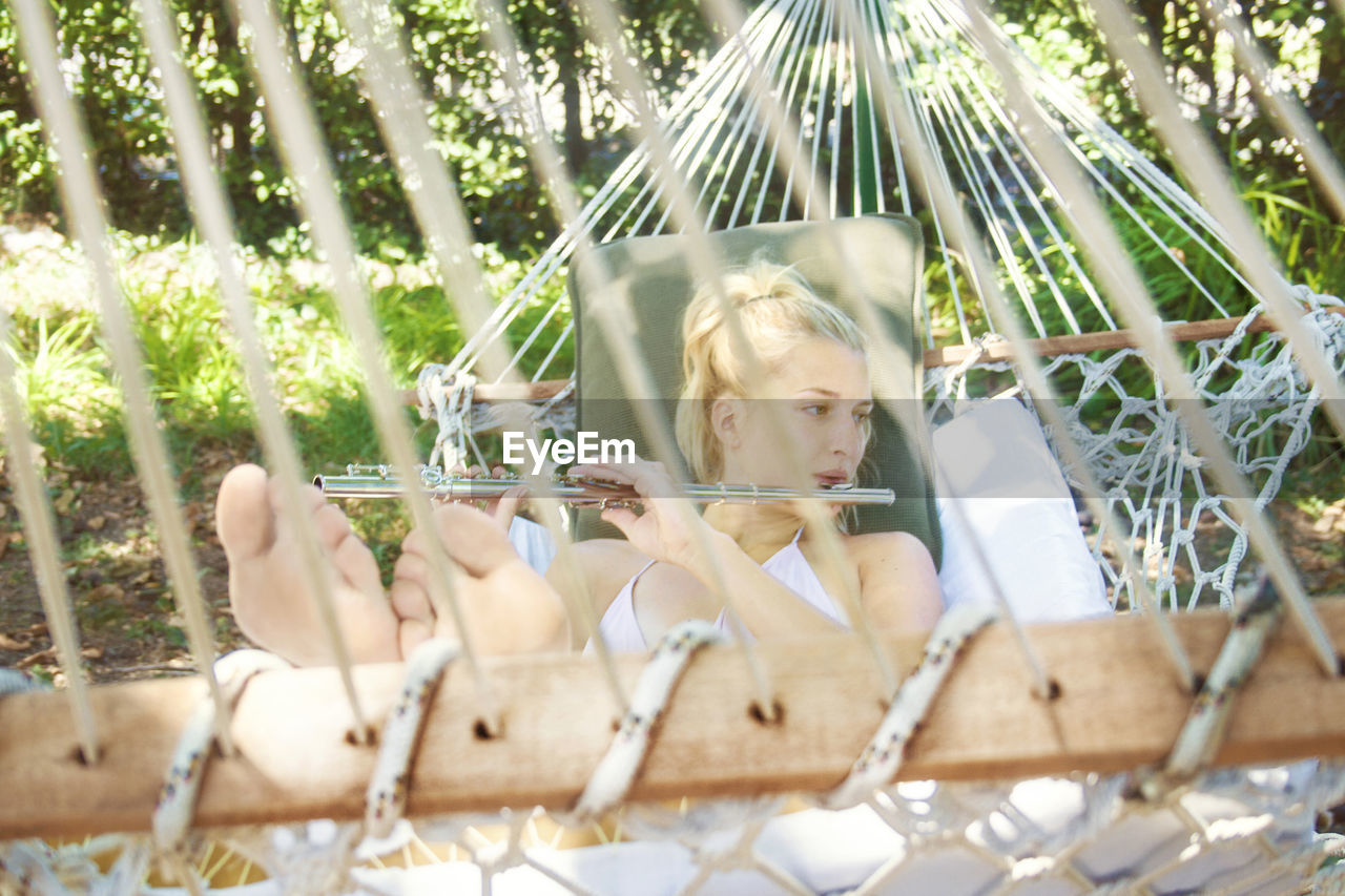 Beautiful Young Woman Playing Flute While Lying On Hammock