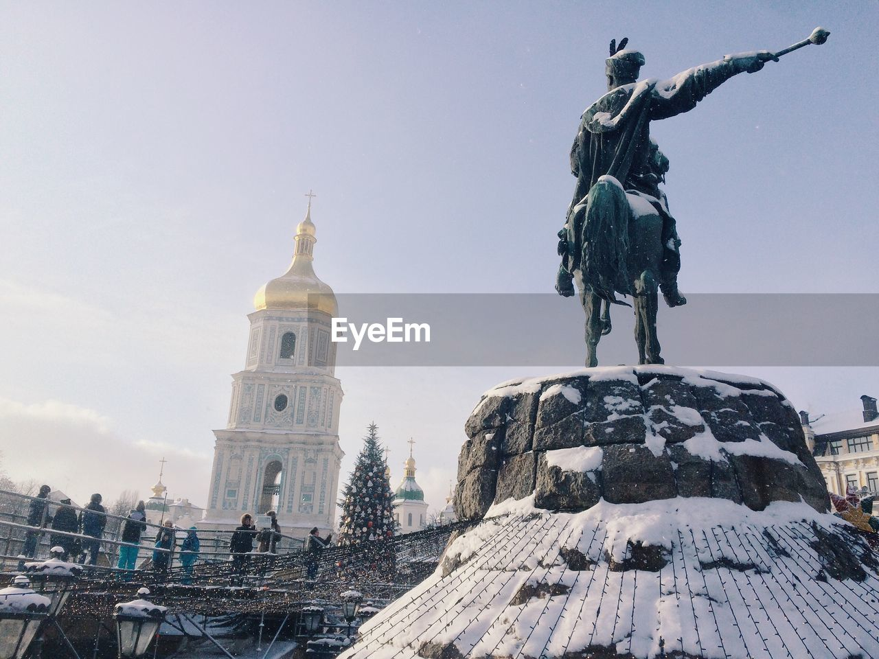 People looking at snow covered statue against church during christmas