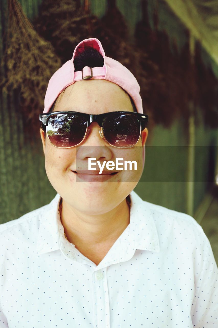 Portrait of smiling woman wearing sunglasses and cap