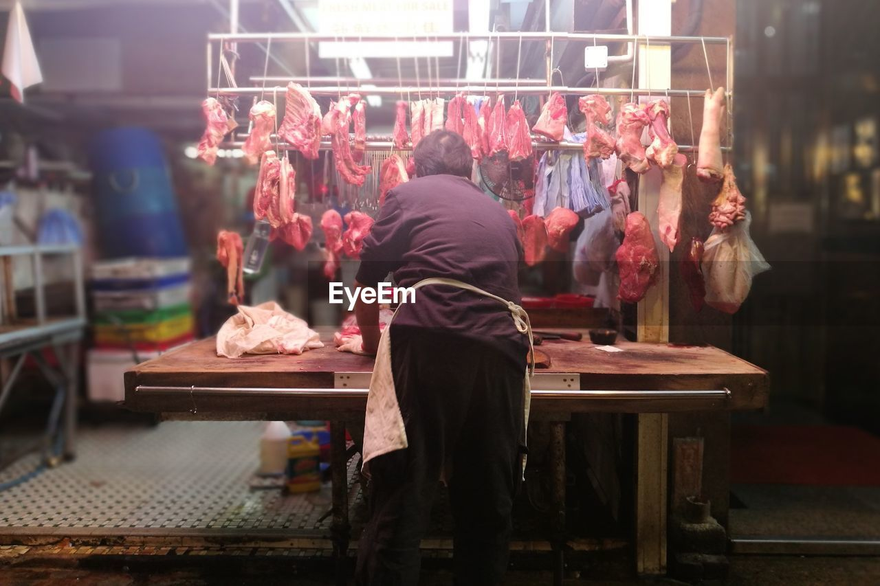 Rear View Of Butcher With Fresh Meat In Shop