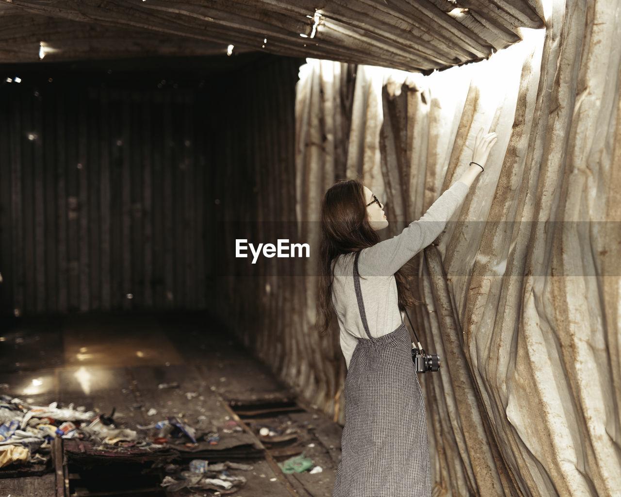 Side view of woman touching broken metal wall