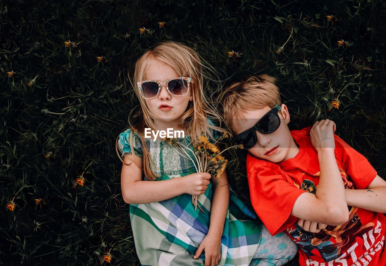 High angle portrait of girl and boy wearing sunglasses while lying on grass