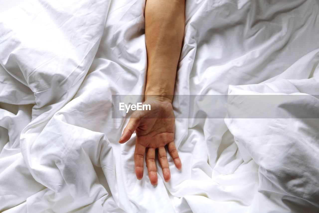 Cropped Image Of Man Hand On Crumpled Blanket At Bed
