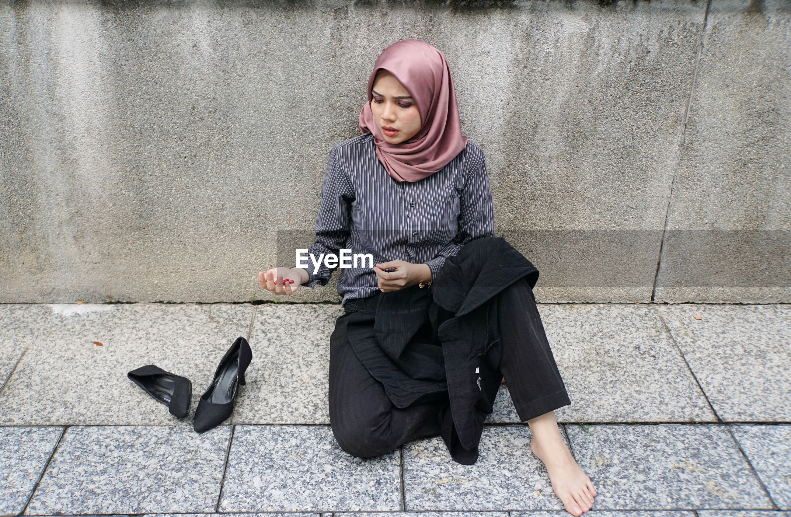 Full length of a young woman sitting on concrete wall