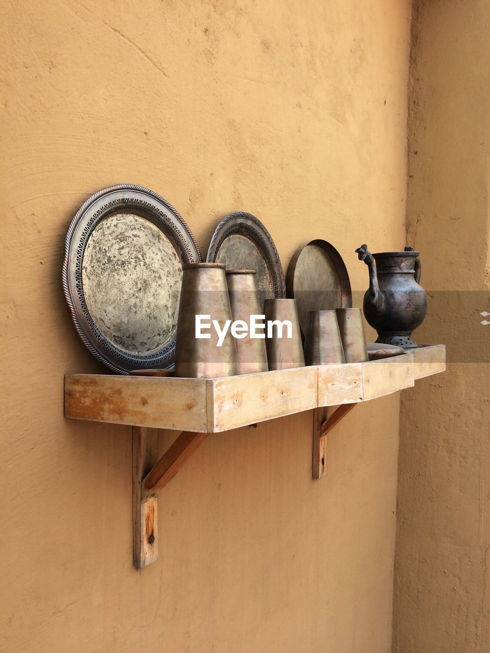 Old utensils and plates on shelf against wall