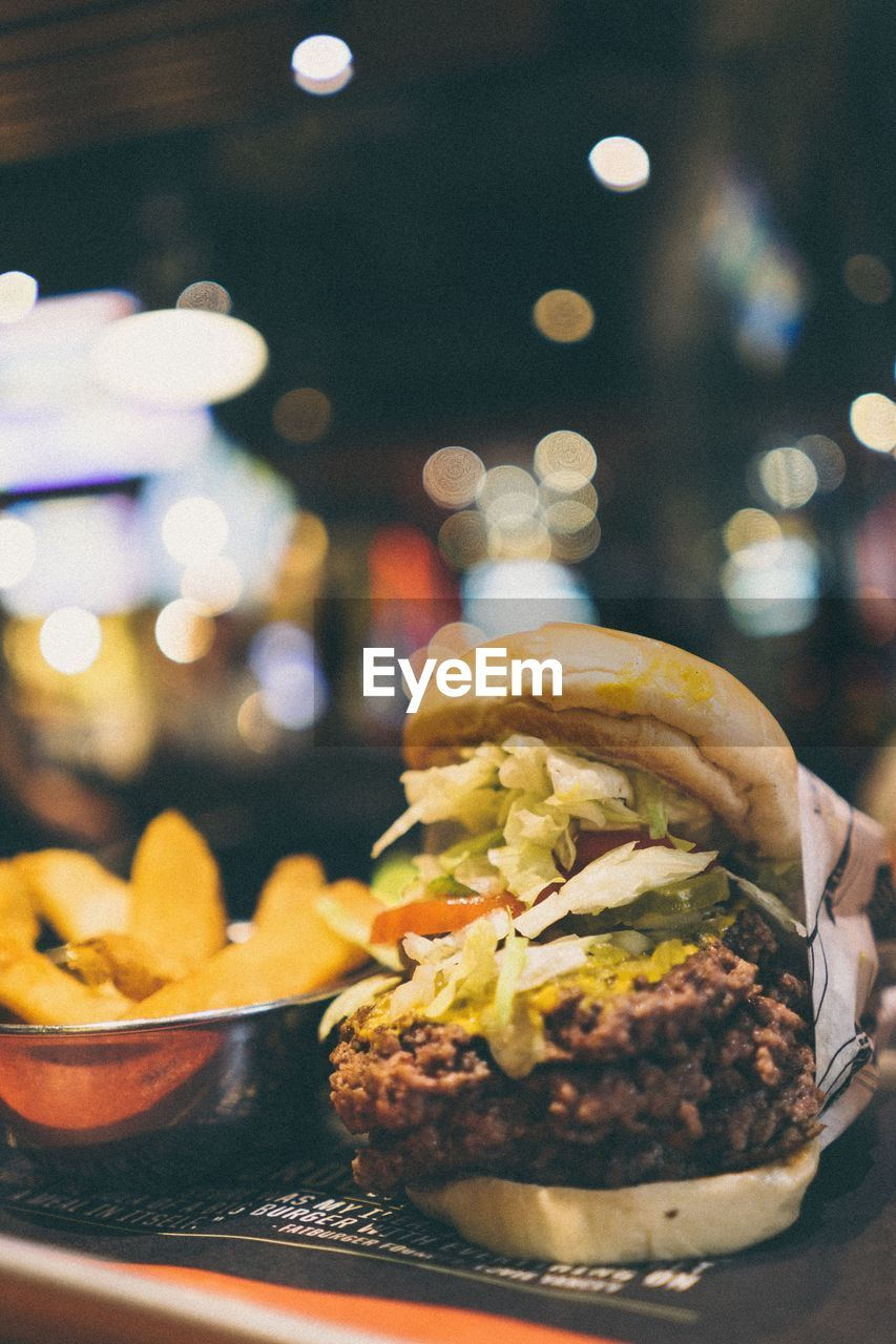 Close-Up Of Hamburger On Table At Sidewalk Cafe