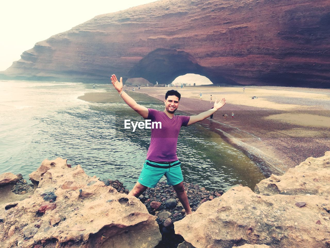one person, real people, solid, water, human arm, leisure activity, rock, rock - object, lifestyles, beauty in nature, full length, scenics - nature, sea, rock formation, limb, nature, young men, casual clothing, arms outstretched, freedom, outdoors, arms raised