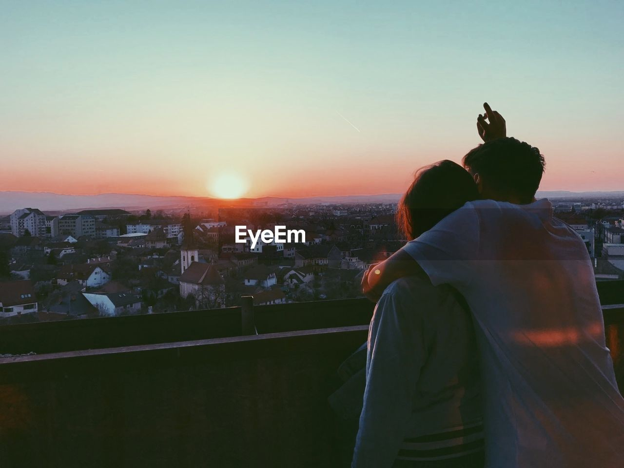architecture, sky, building exterior, built structure, city, two people, real people, sunset, lifestyles, cityscape, men, leisure activity, togetherness, rear view, standing, nature, people, adult, women, waist up, outdoors, looking at view, couple - relationship