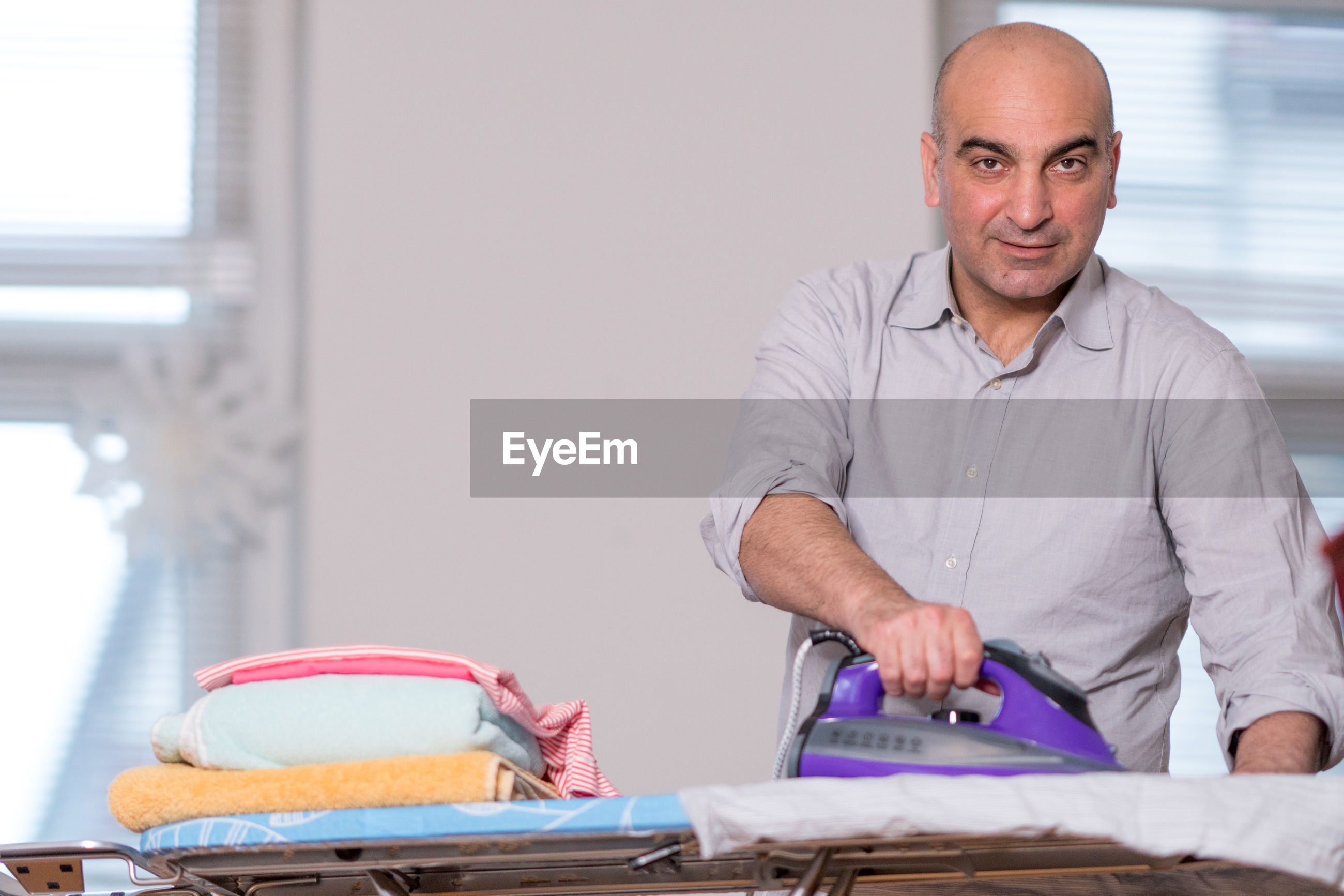 Portrait of man ironing clothes at home