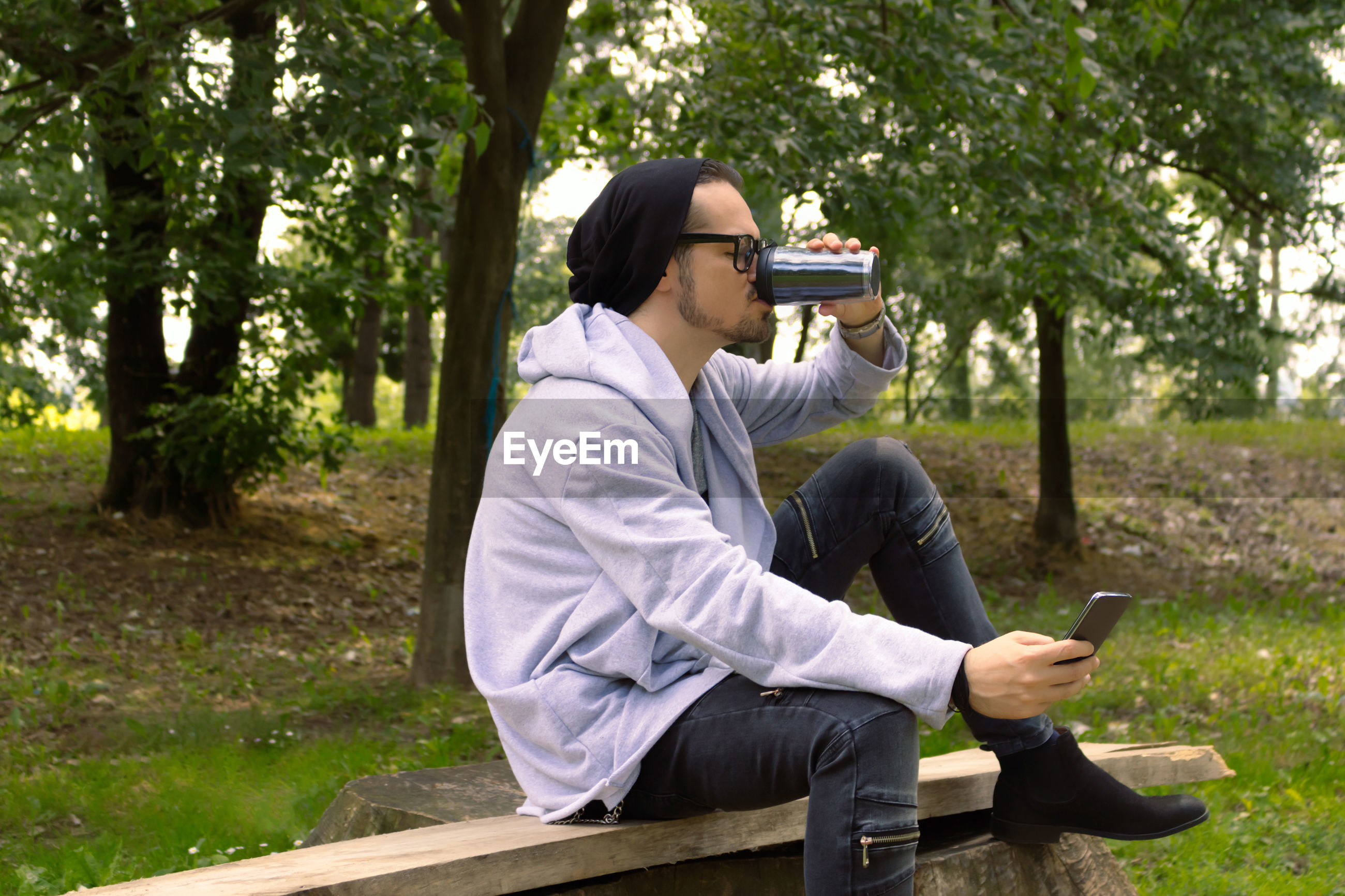 REAR VIEW OF MAN USING MOBILE PHONE WHILE SITTING IN PARK