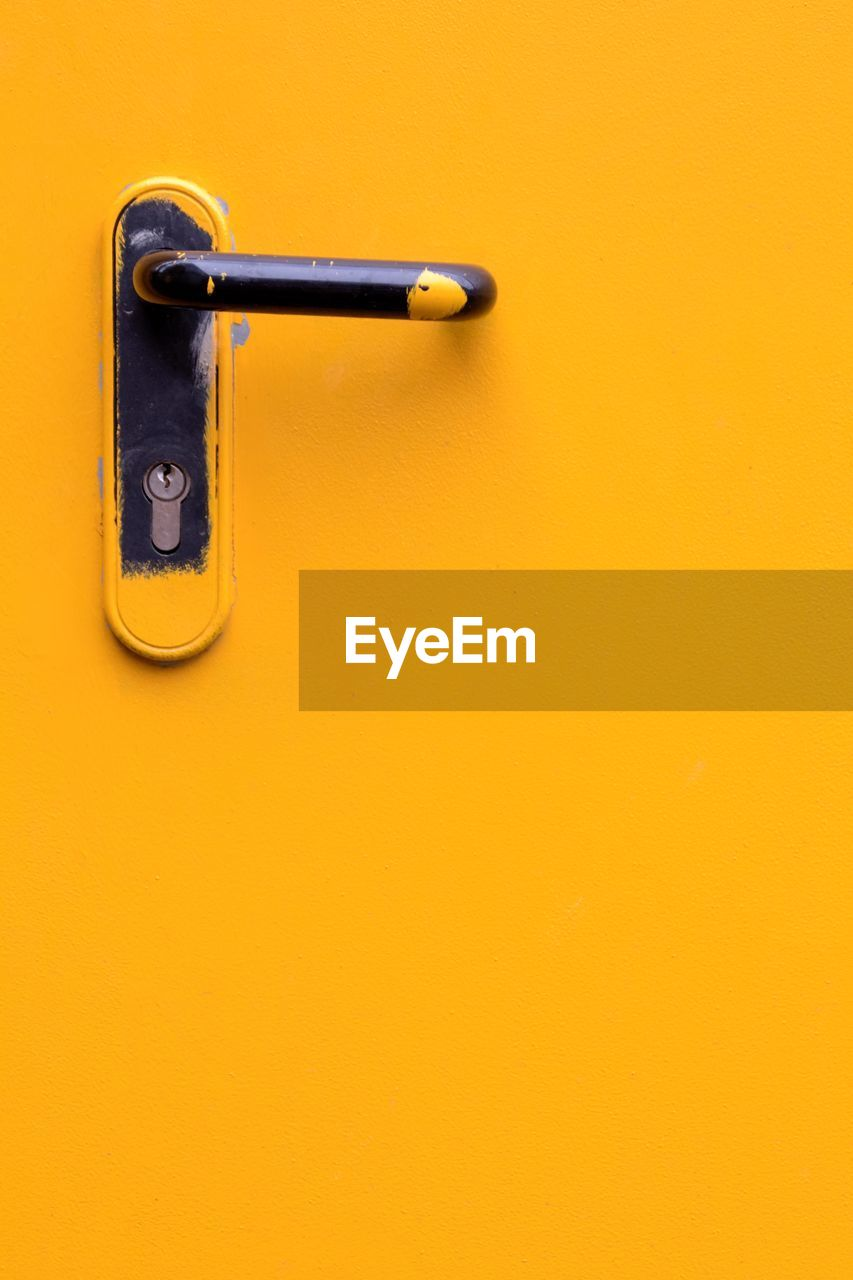 yellow, metal, no people, copy space, close-up, safety, indoors, still life, protection, orange color, security, single object, studio shot, handle, lock, wall - building feature, colored background, built structure, equipment, day