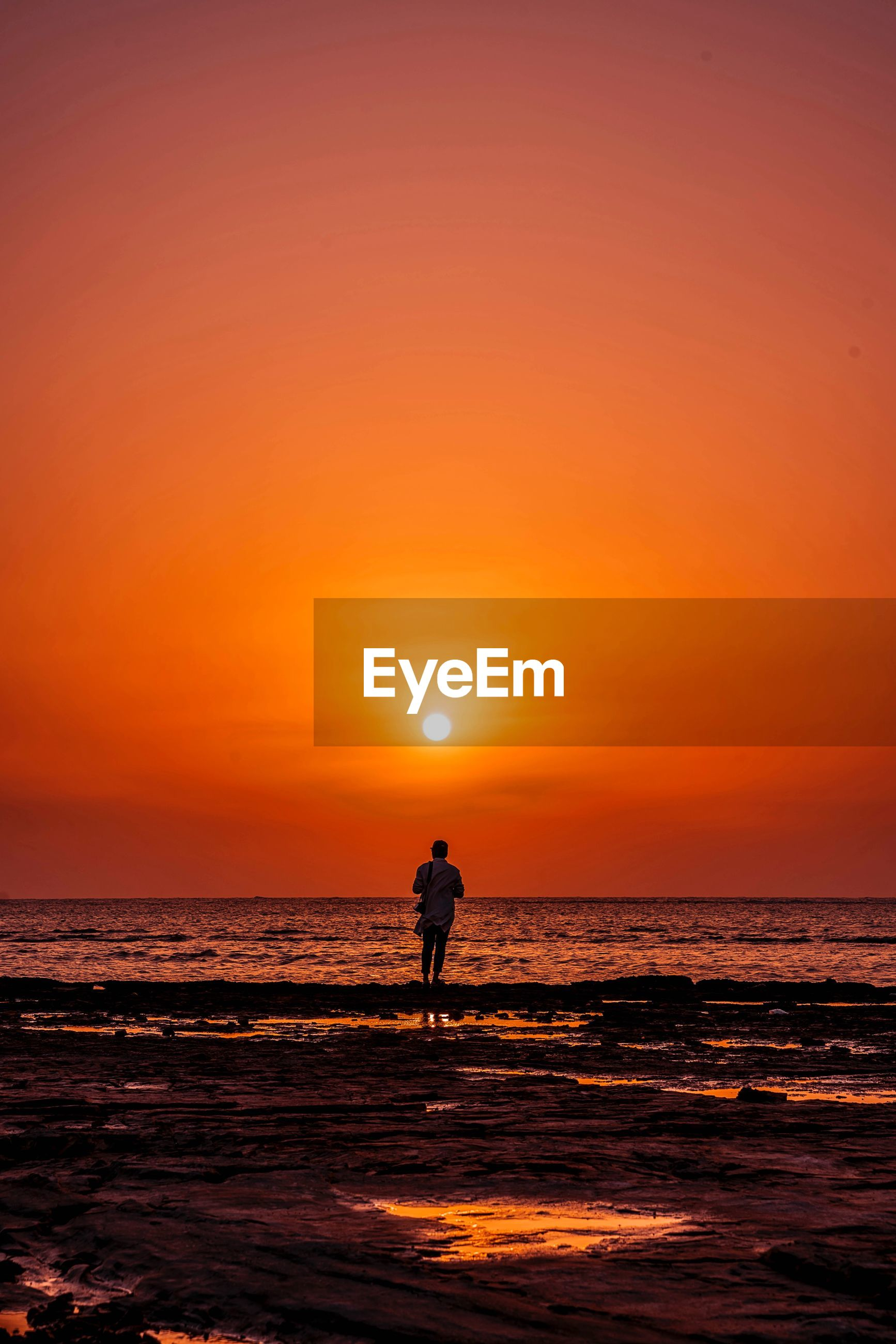 sunset, sea, sky, orange color, water, horizon over water, horizon, scenics - nature, beauty in nature, silhouette, real people, land, beach, one person, sun, lifestyles, leisure activity, nature, full length, outdoors