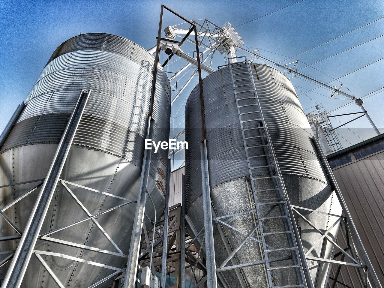 factory, low angle view, industry, storage tank, metal, no people, built structure, industrial building, silo, day, building exterior, sky, architecture, oil industry, steel, outdoors, technology, metal industry, petrochemical plant, close-up
