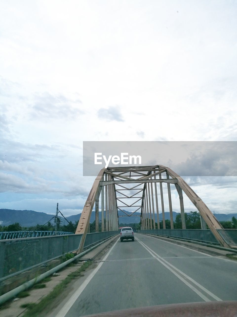 sky, bridge - man made structure, connection, cloud - sky, transportation, day, road, the way forward, outdoors, built structure, architecture, suspension bridge, no people, city