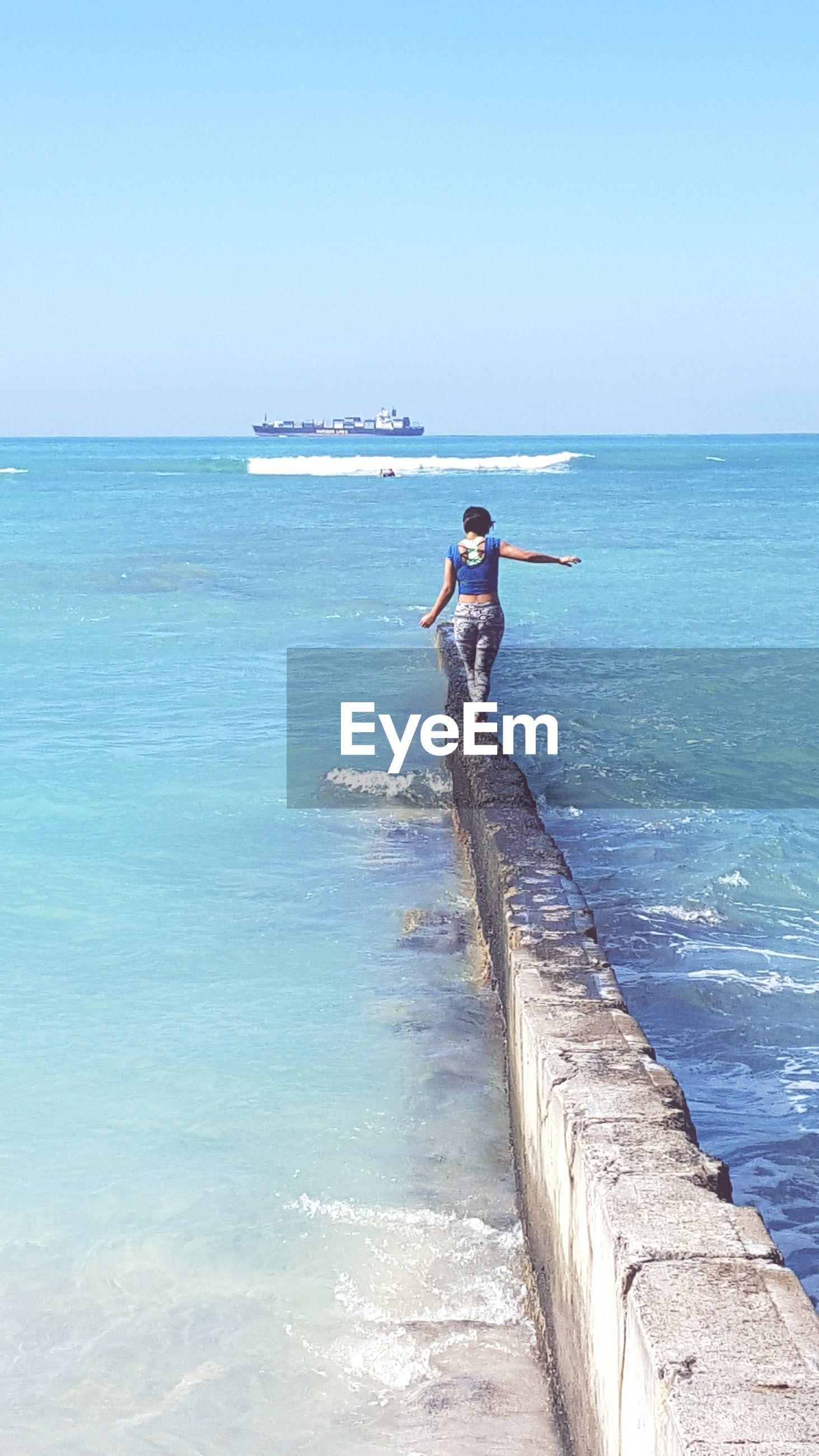 Rear view of woman walking on groyne against sea