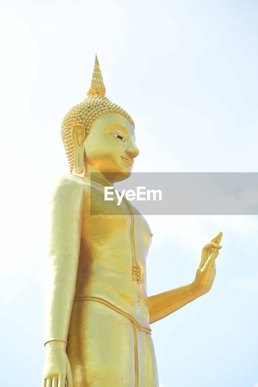 religion, spirituality, belief, sculpture, representation, human representation, sky, statue, male likeness, low angle view, art and craft, place of worship, gold colored, day, creativity, no people, nature, idol