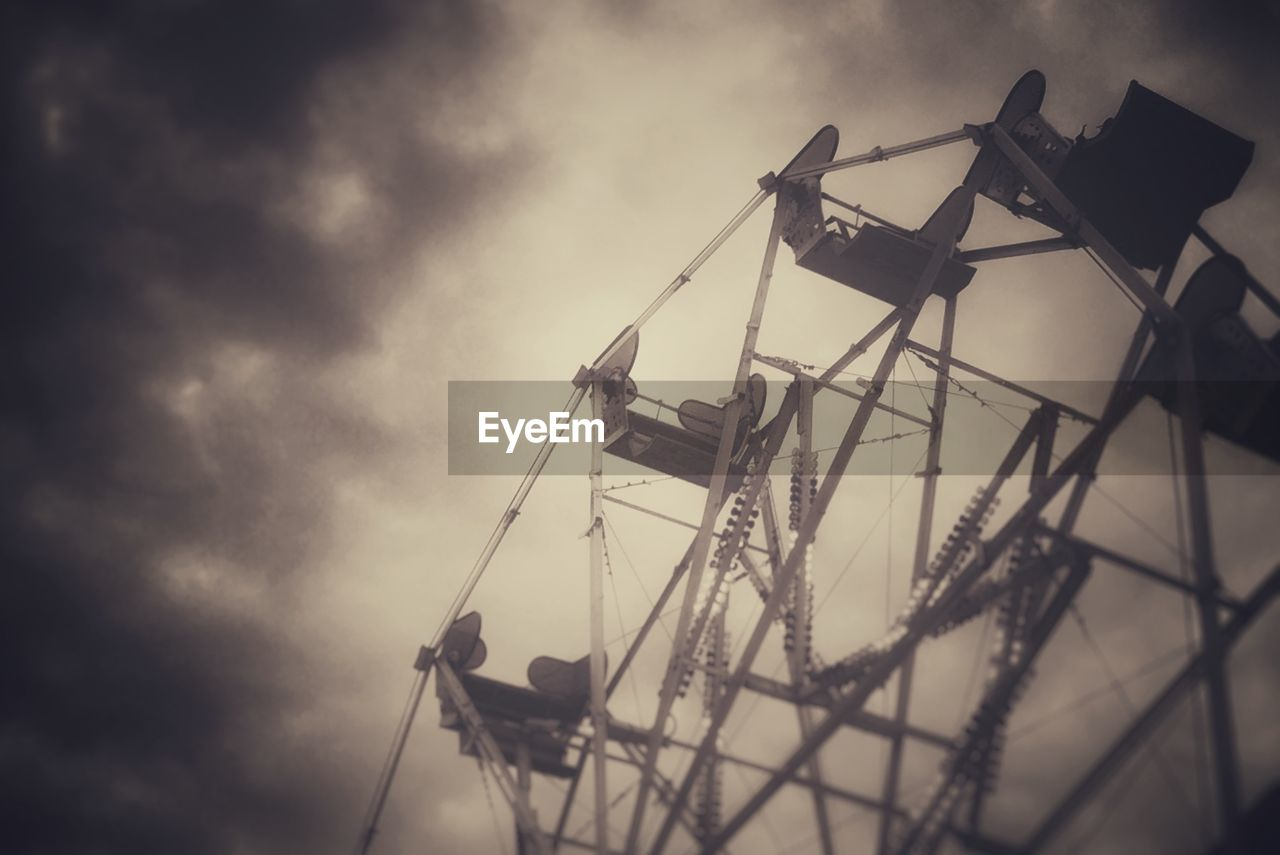 Low angle view of ferris wheel at amusement park against cloudy sky