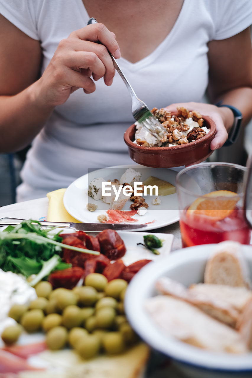 food and drink, food, freshness, real people, midsection, healthy eating, one person, indoors, table, men, wellbeing, plate, bowl, holding, human hand, meal, kitchen utensil, selective focus, eating utensil, hand
