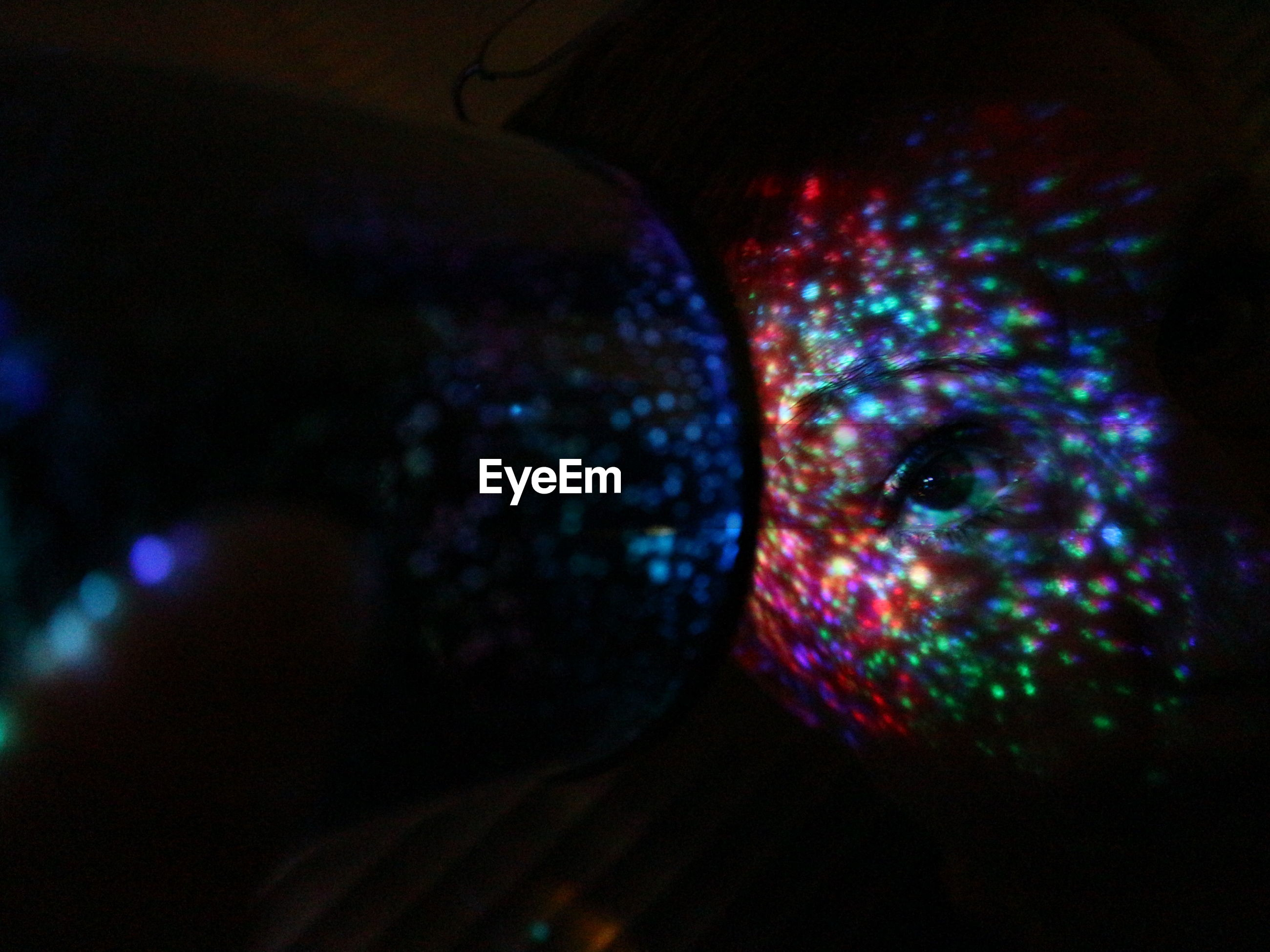 Close-up of colorful lights falling on woman face in darkroom