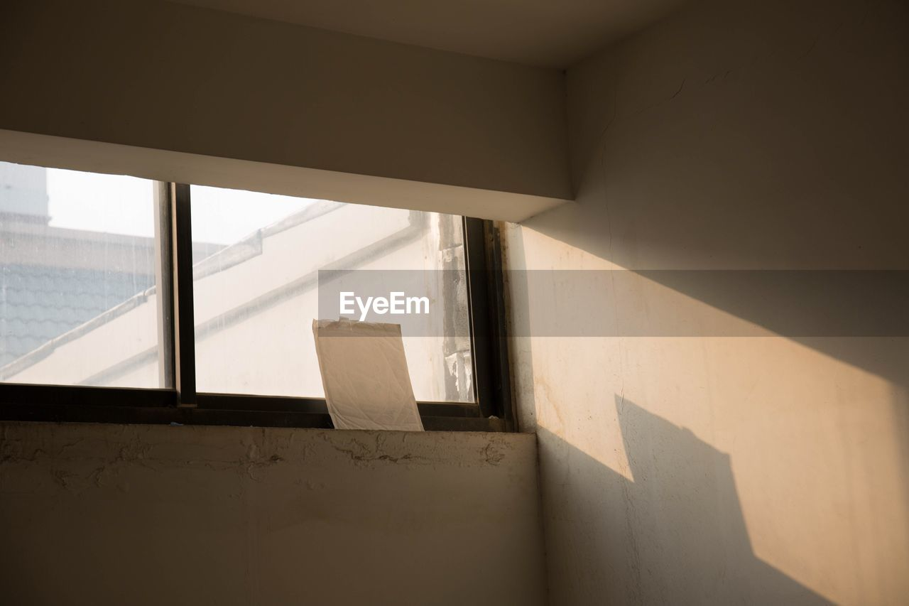 architecture, sunlight, shadow, wall - building feature, window, indoors, day, built structure, no people, staircase, home interior, steps and staircases, wall, nature, building, house, white color, low angle view, glass - material, focus on shadow
