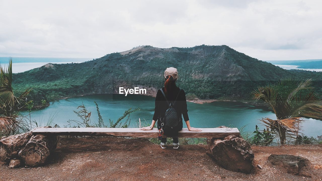 Full Length Of Woman Looking At View While Sitting By Lake Against Sky