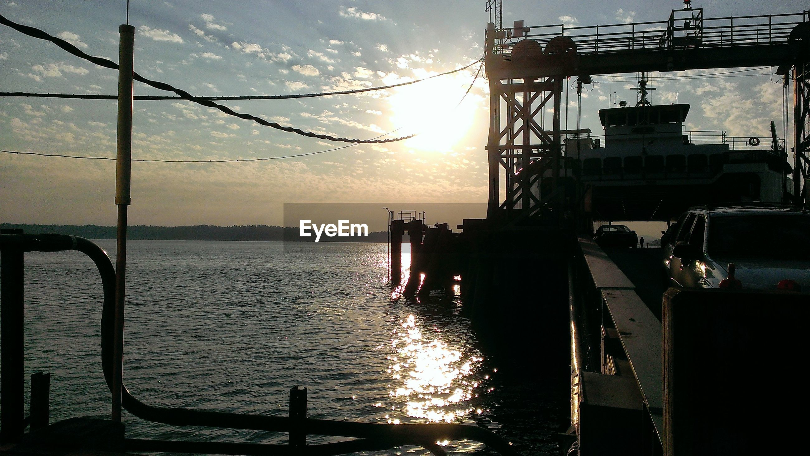 Cars being transported by ferry at harbor during sunset
