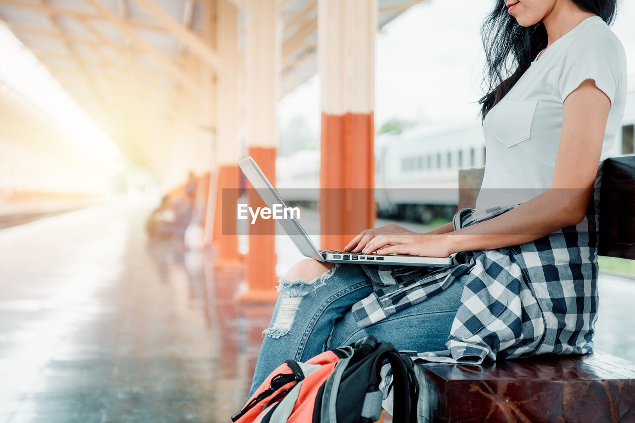 real people, one person, laptop, wireless technology, casual clothing, using laptop, young women, connection, women, adult, lifestyles, focus on foreground, computer, technology, young adult, three quarter length, leisure activity, sitting, communication, hairstyle, outdoors