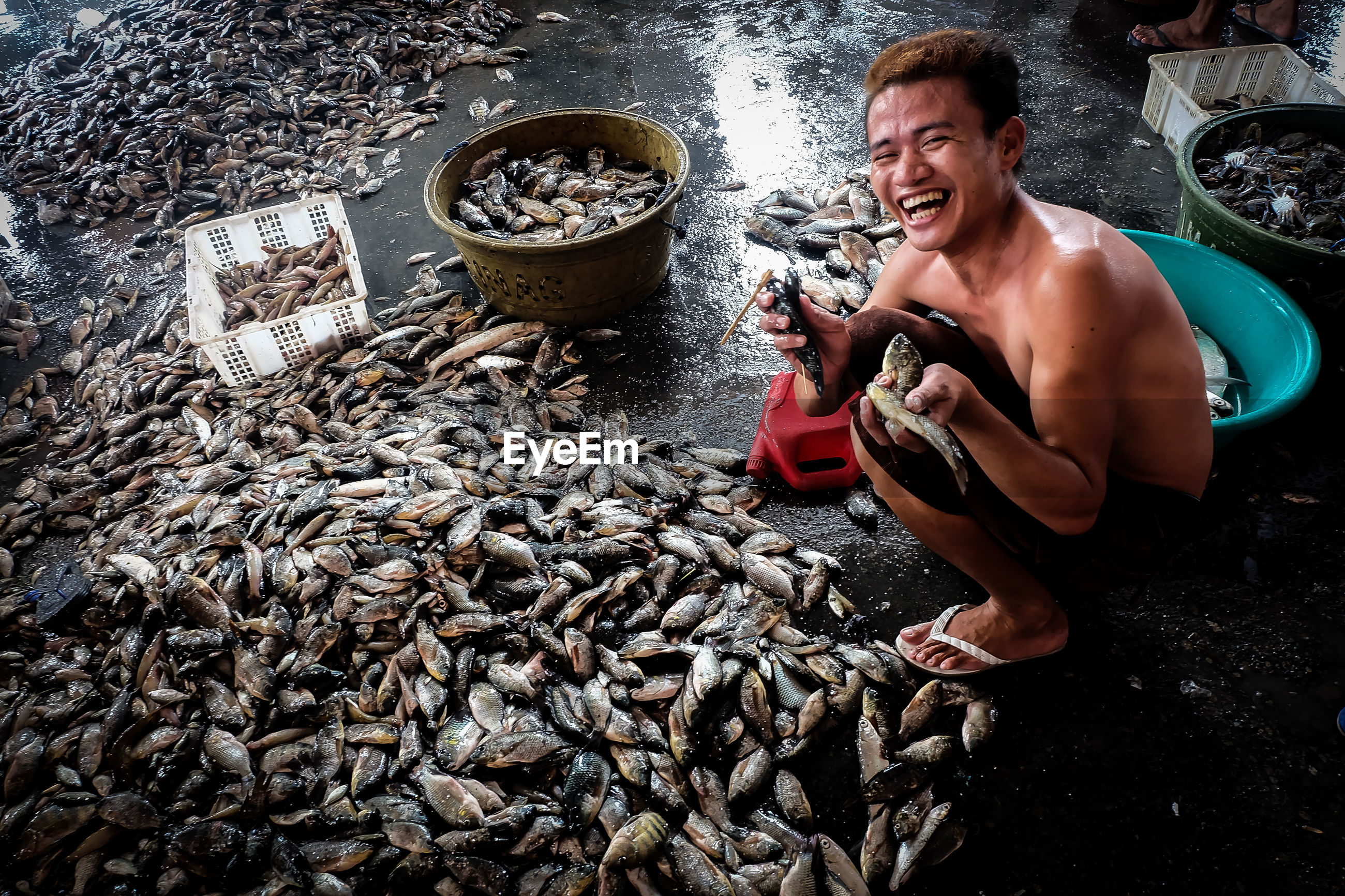 Portrait of happy man holding fishes in market