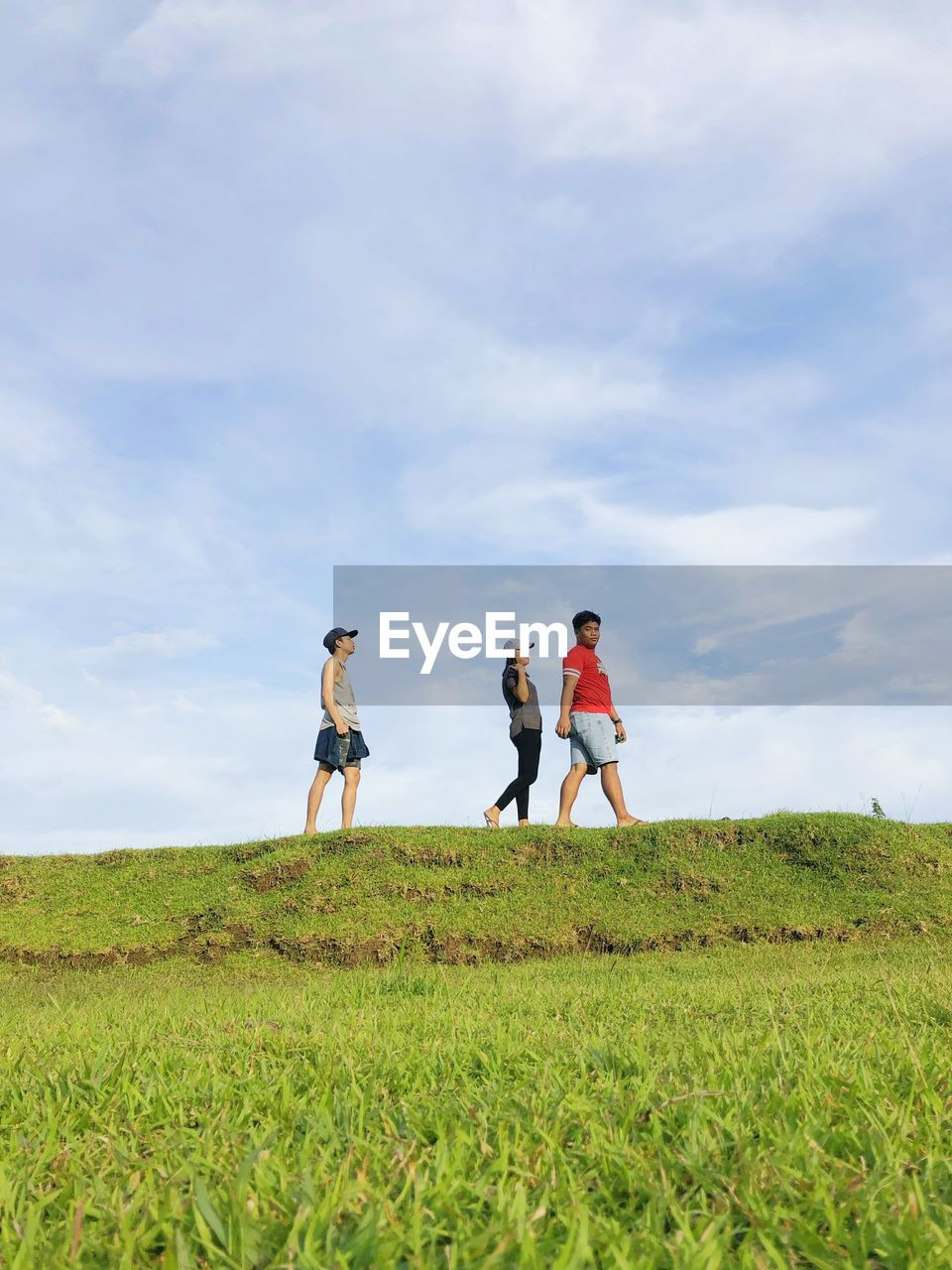 sky, cloud - sky, grass, women, field, real people, land, plant, lifestyles, adult, nature, group of people, beauty in nature, leisure activity, day, togetherness, green color, full length, men, people, outdoors
