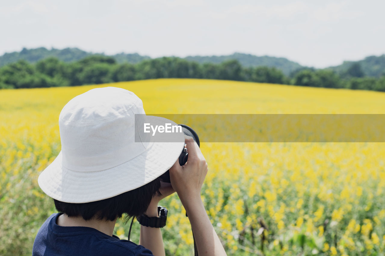 woman wearing hat photographing against sky
