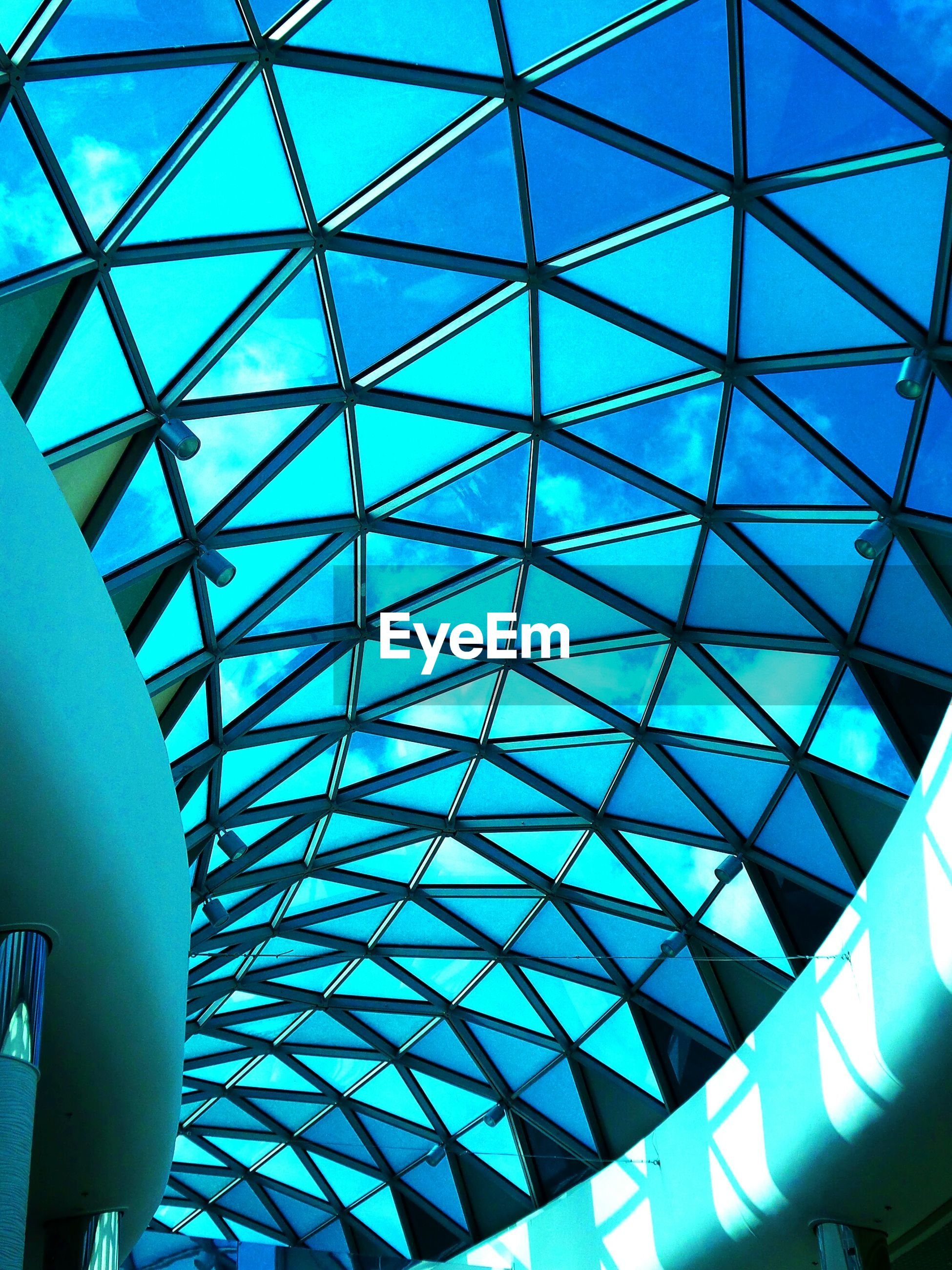 indoors, architecture, glass - material, built structure, low angle view, ceiling, modern, geometric shape, pattern, full frame, backgrounds, architectural feature, glass, transparent, skylight, blue, window, sky, reflection, no people
