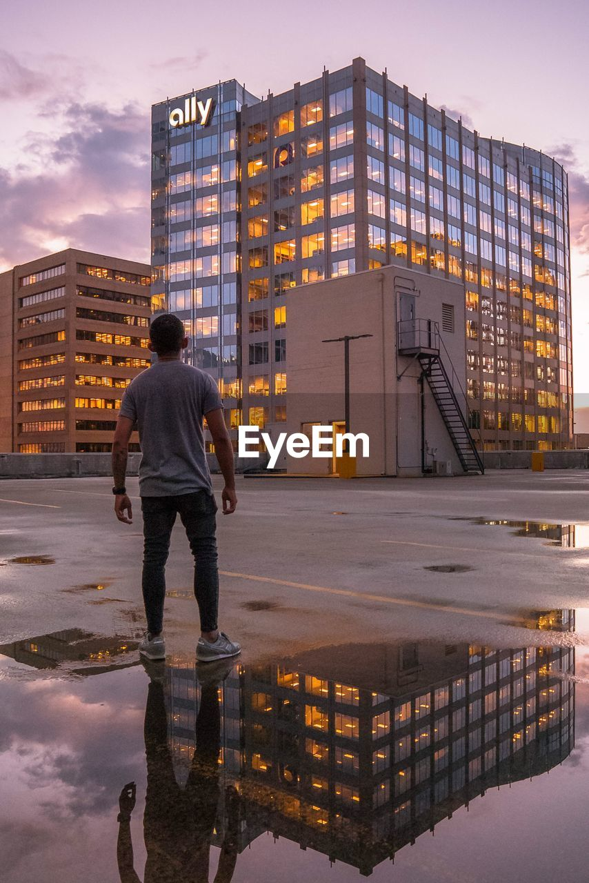 architecture, building exterior, built structure, city, one person, rear view, building, full length, sky, standing, real people, sunset, reflection, men, lifestyles, nature, water, leisure activity, office building exterior, modern, outdoors, cityscape, skyscraper