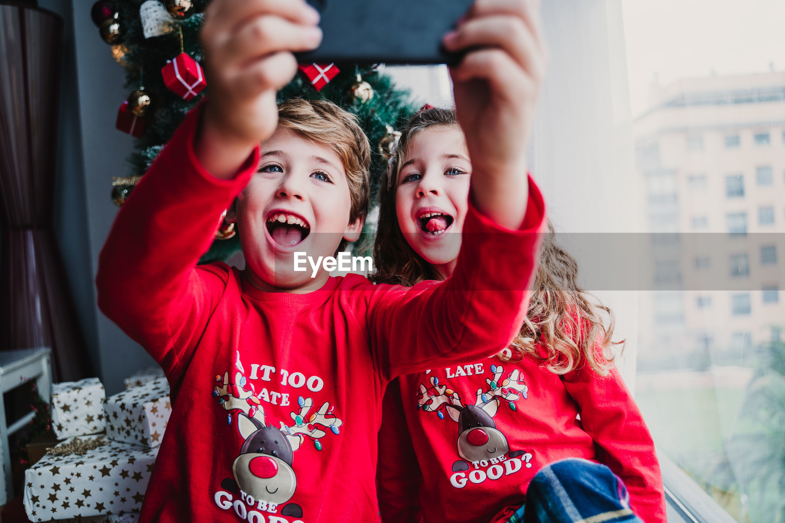 Brother and sister at home taking a selfie with mobile phone.kids sitting by christmas tree