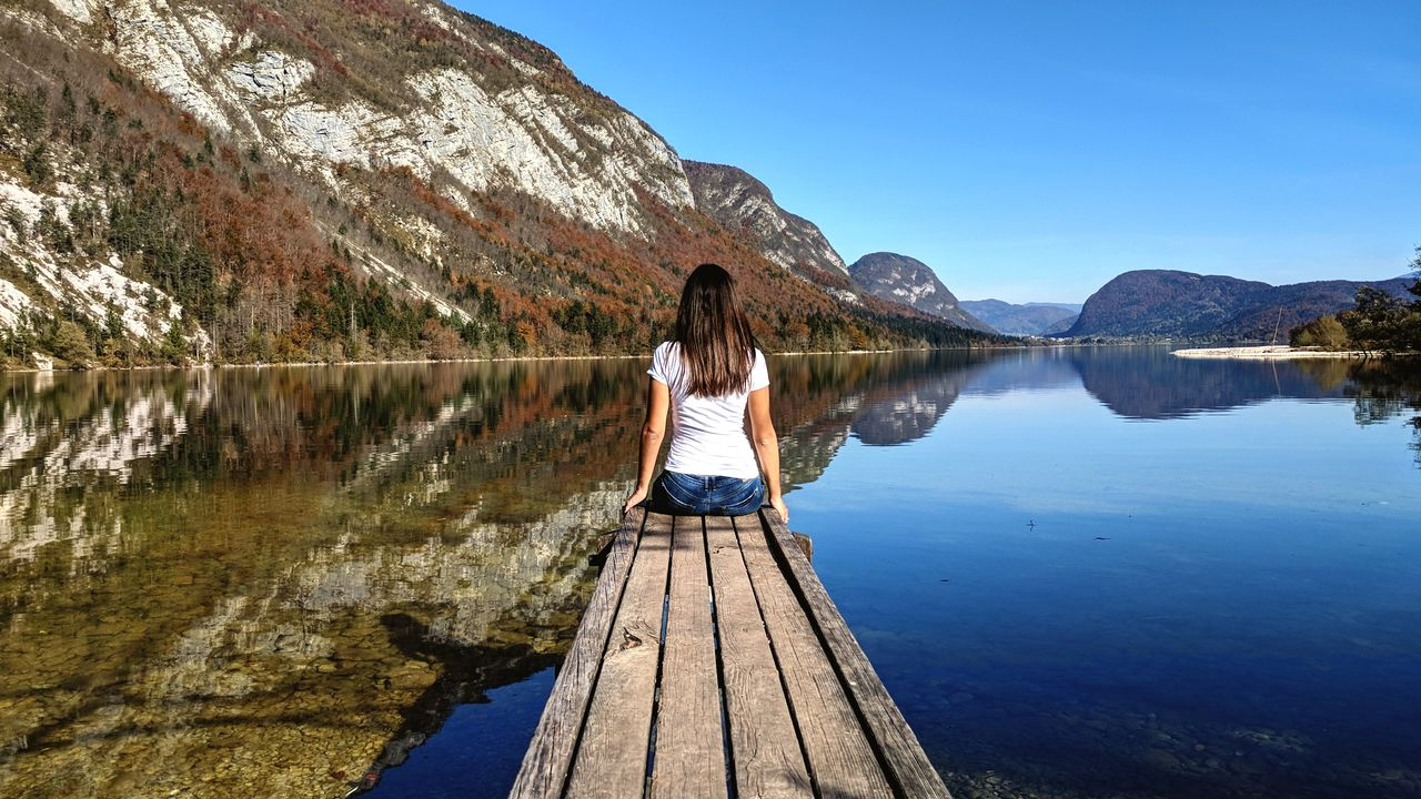 Rear View Of Woman Sitting On Pier By Lake Against Mountains