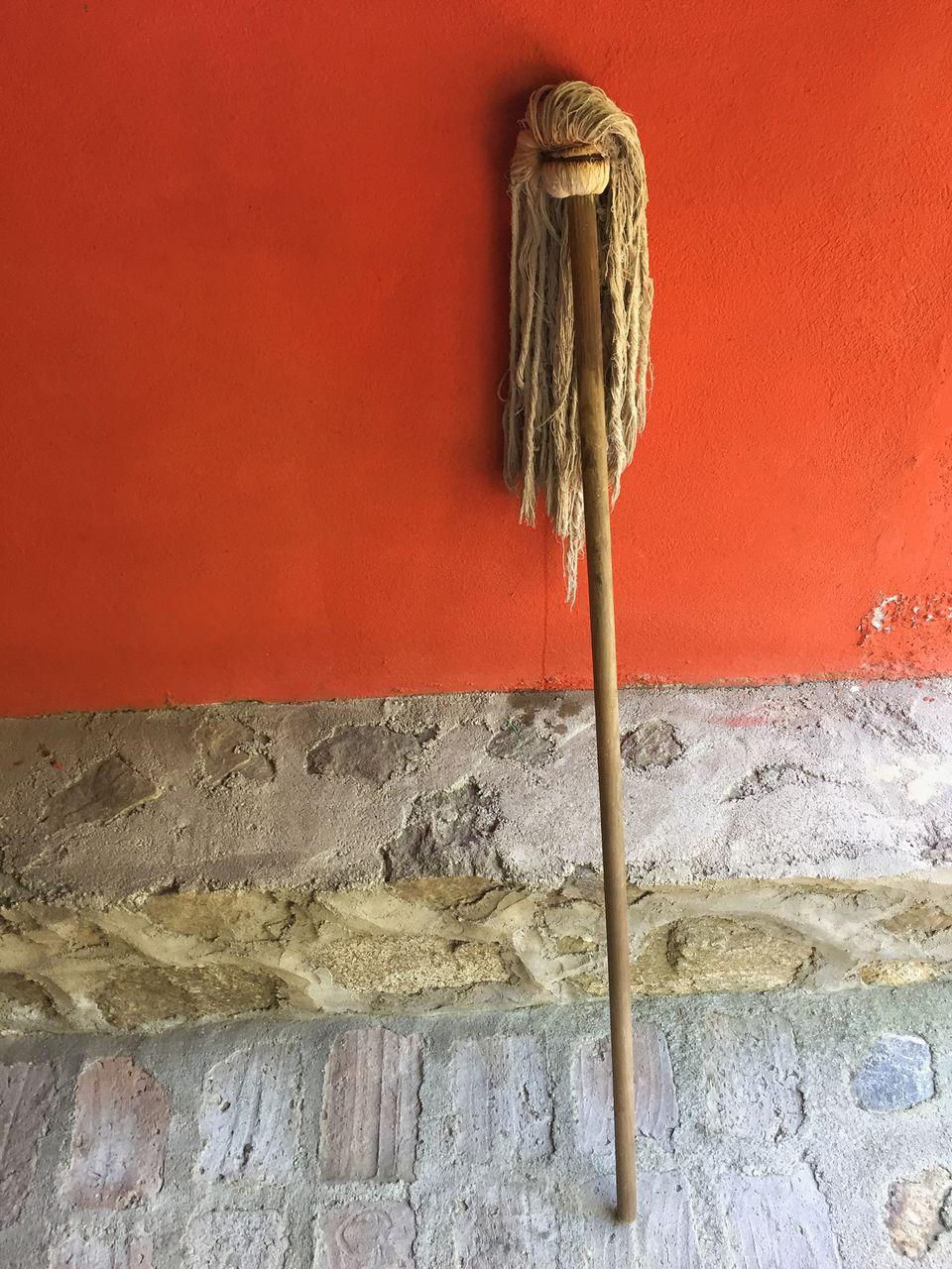 Mop leaning on orange wall