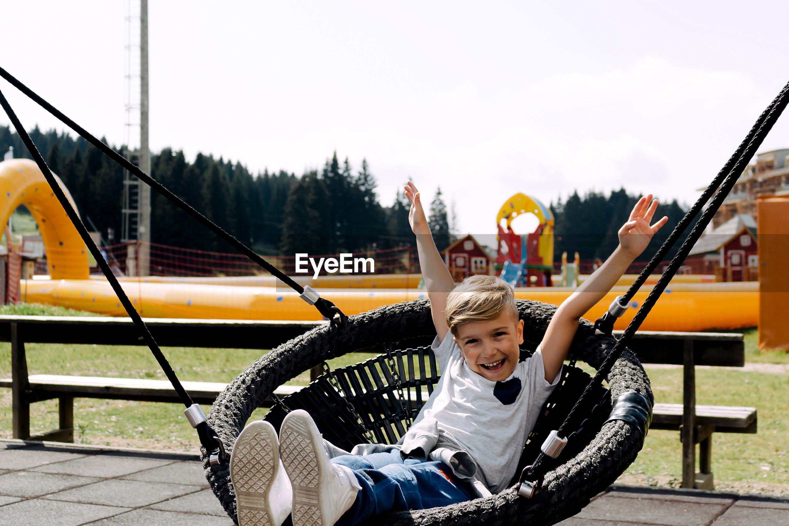 HAPPY BOY SITTING ON SLIDE AT PLAYGROUND AGAINST SKY