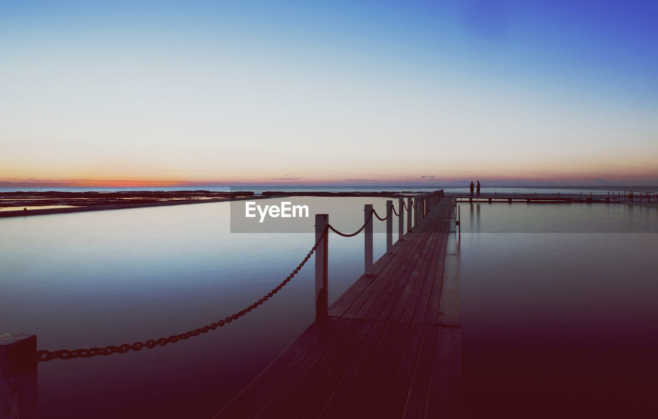 sunset, tranquil scene, beauty in nature, scenics, nature, water, tranquility, sea, railing, outdoors, pier, sky, idyllic, no people, jetty, clear sky, horizon over water, day
