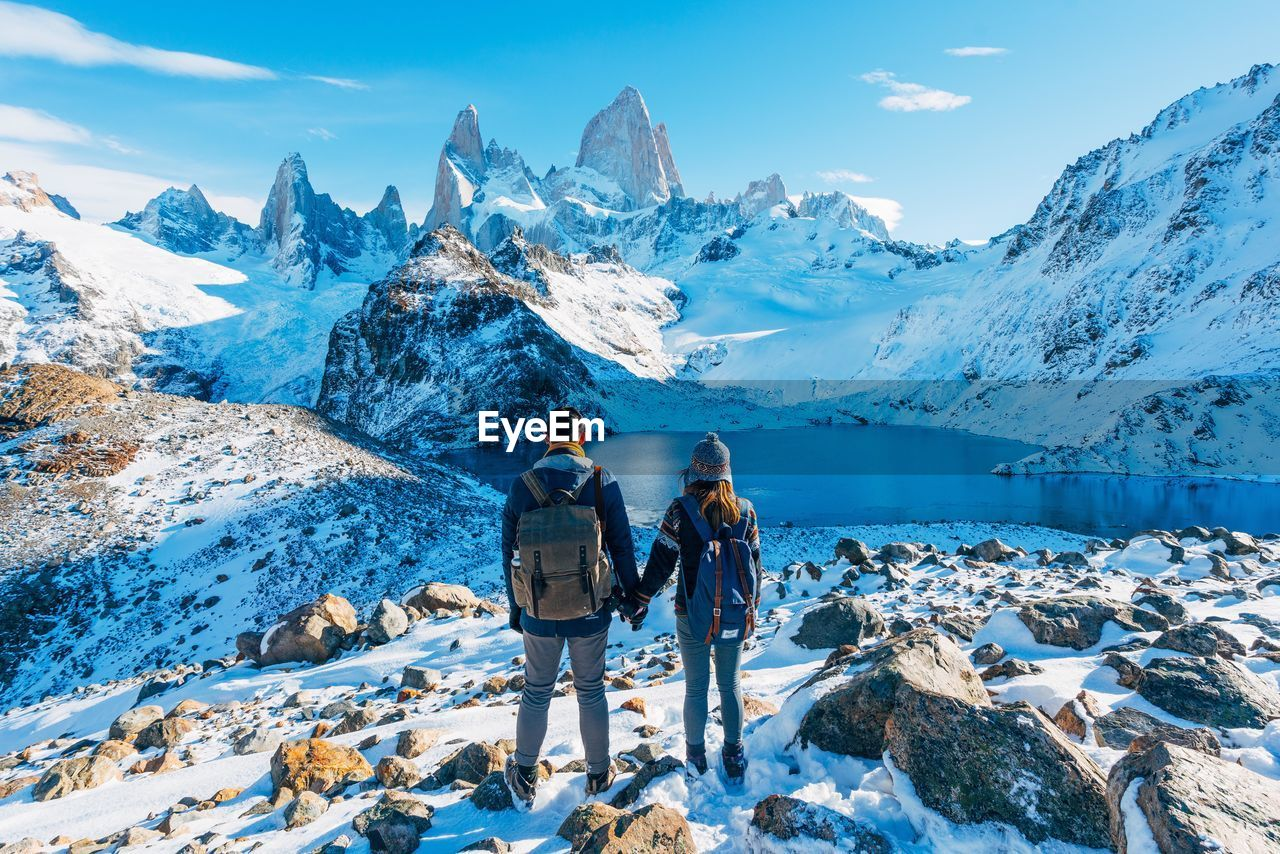 Rear View Of Young Couple With Backpacks Standing On Field Against Sky During Winter