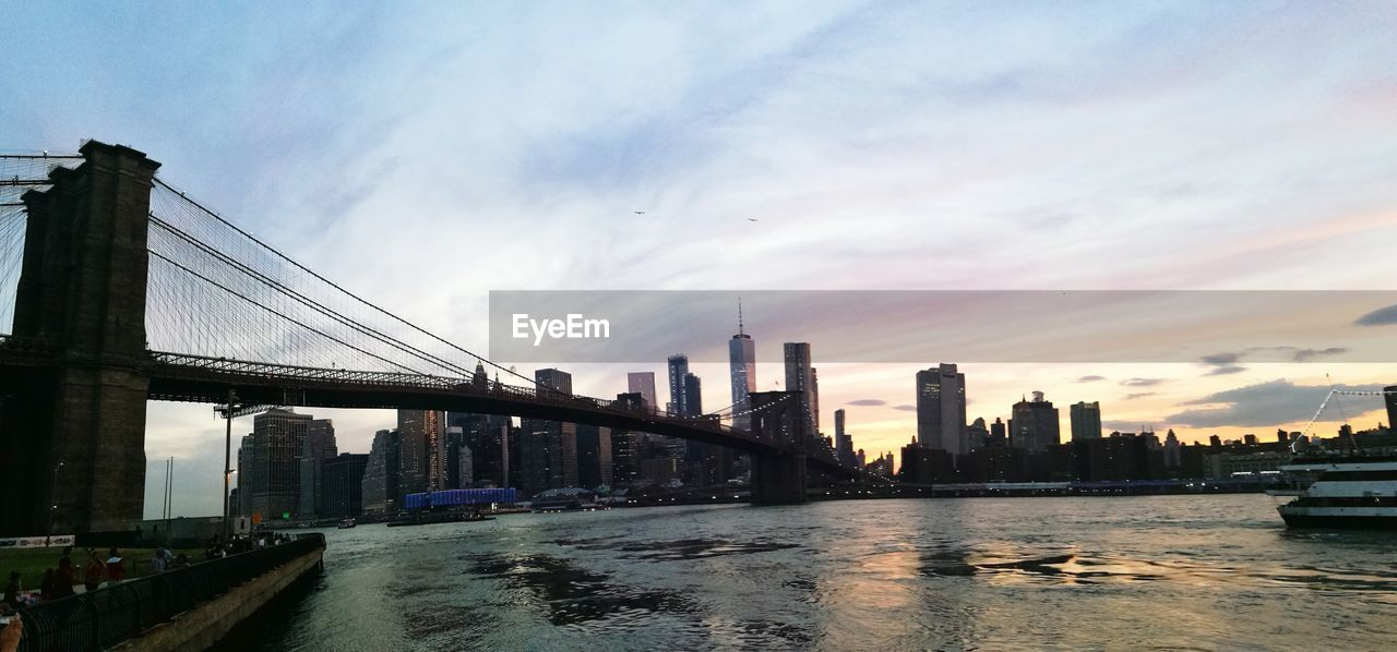 architecture, built structure, water, building exterior, sky, city, bridge, building, connection, bridge - man made structure, cloud - sky, urban skyline, transportation, office building exterior, skyscraper, nature, waterfront, river, cityscape, tall - high, no people, outdoors, financial district, modern, bay