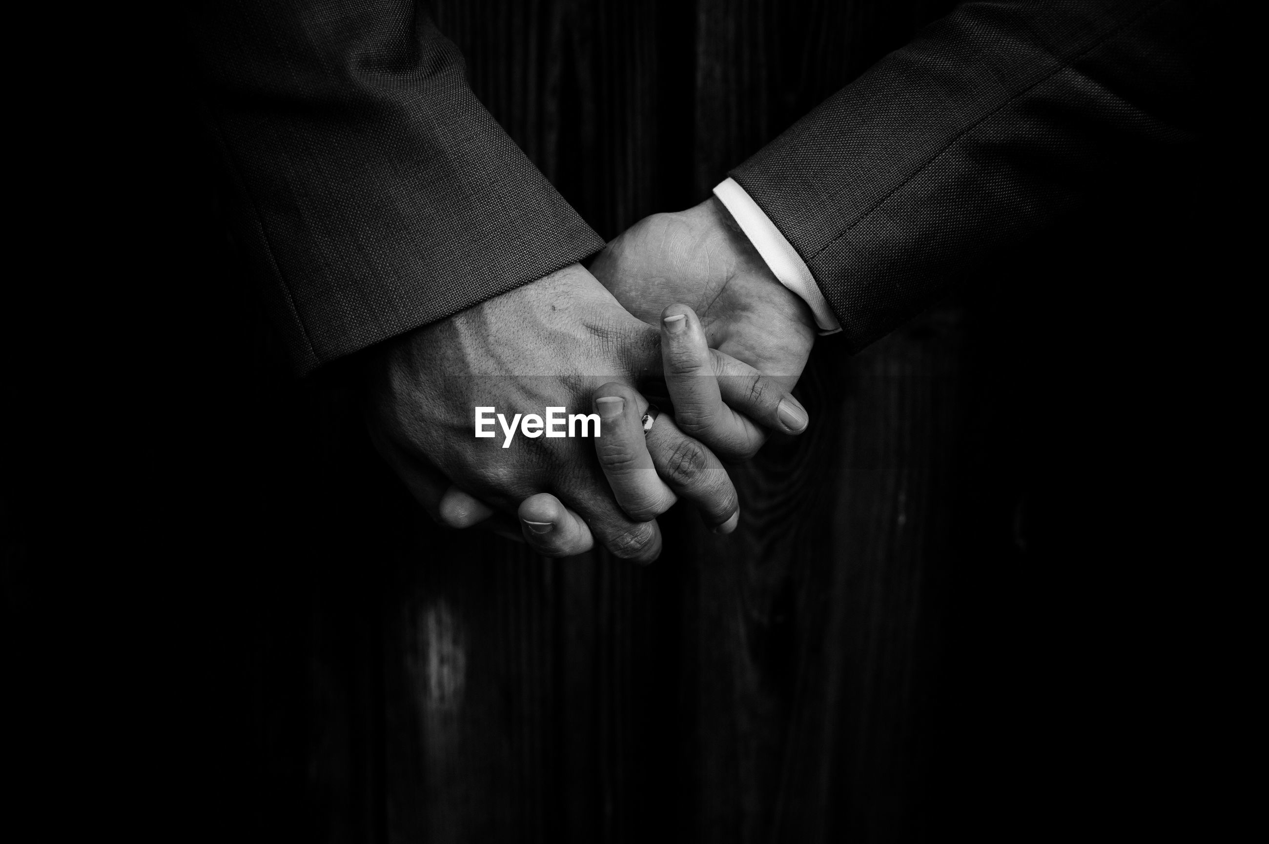 Close-up of gay men holding hands in dark