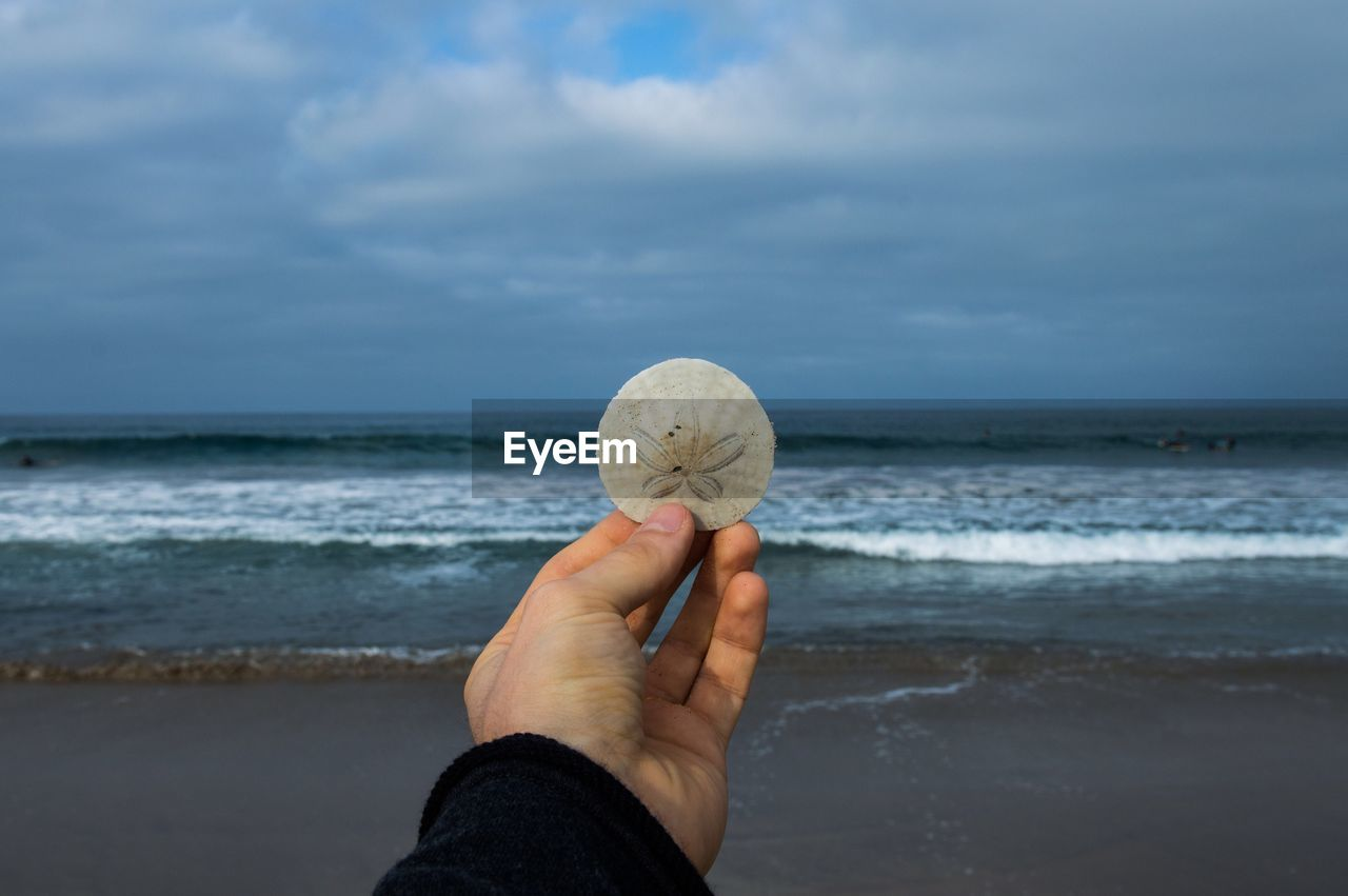 MAN HAND WITH BALL ON BEACH