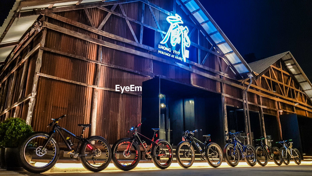 bicycle, transportation, night, mode of transport, land vehicle, outdoors, stationary, illuminated, architecture, building exterior, helmet, bicycle rack, no people