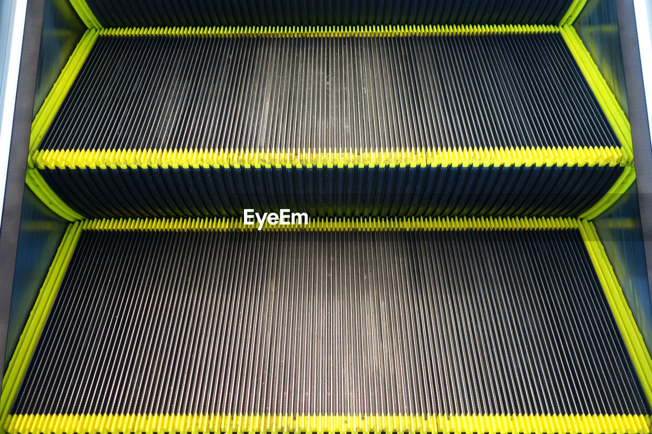 technology, escalator, no people, pattern, metal, close-up, indoors, high angle view, yellow, modern, backgrounds, equipment, abstract, industry, machinery, factory, full frame, motion, connection, black color, moving walkway, silver colored